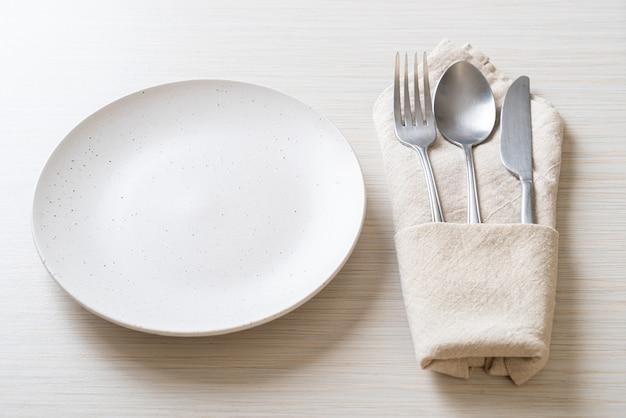 Piatto vuoto o piatto con coltello, forchetta e cucchiaio sul tavolo delle mattonelle di legno