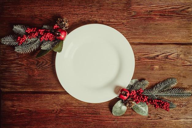 Piatto vuoto del piatto con spazio per testo e due brunch decorativi dell'abete su fondo di legno scuro. concetto tradizionale dell'alimento di celebrazione di natale e del nuovo anno.