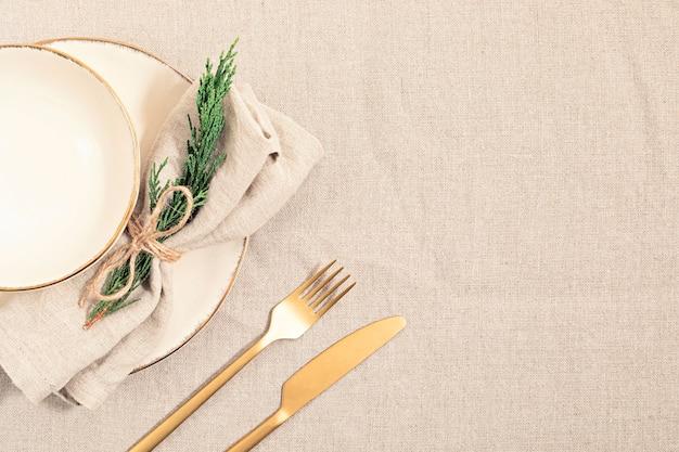 Piatto vuoto e rami di abete su tovaglia di lino in colori neutri naturali. vista piana laico e dall'alto