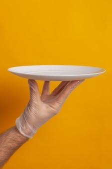 Piatto vuoto tenuto da una mano con guanto di protezione