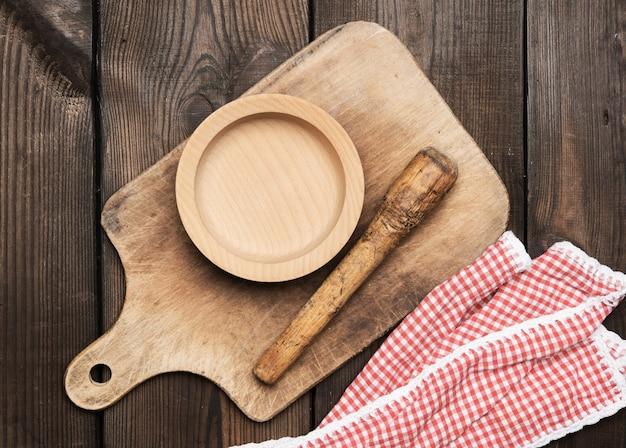 Piatto vuoto e vecchio tagliere da cucina in legno rettangolare marrone sul tavolo, vista dall'alto