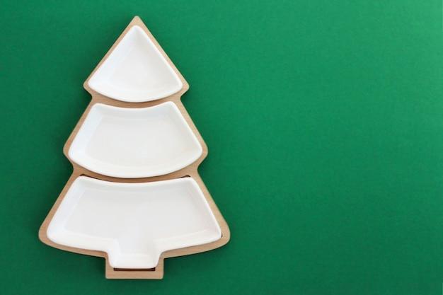 Piatto vuoto a forma di albero di natale su sfondo verde.