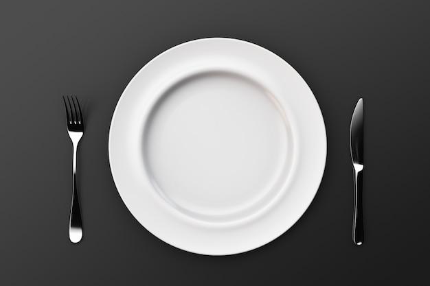 Un piatto vuoto su un tavolo e una forchetta con un coltello. vista dall'alto