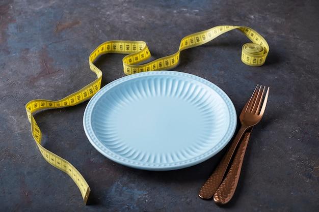 Piatto vuoto con forchetta e coltello vicino al nastro di misurazione. concetto di perdita di peso. stile di vita