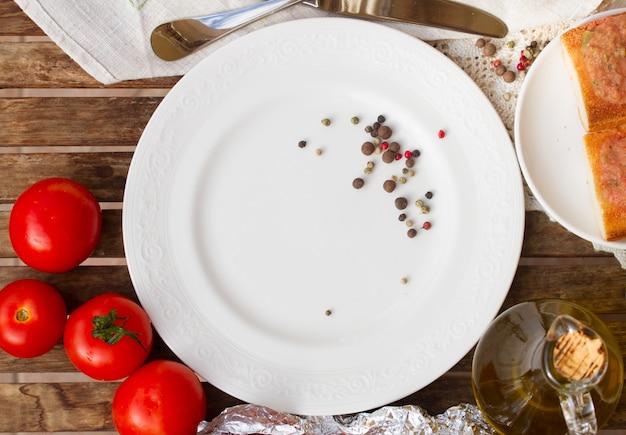 Piatto vuoto con pomodori e olio d'oliva