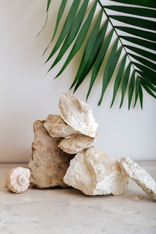Torre vuota delle pietre del podio. pietre grigie display piedistallo su sfondo beige da pietre conchiglia foglia di palma. sfondo astratto mockup per la presentazione del prodotto.