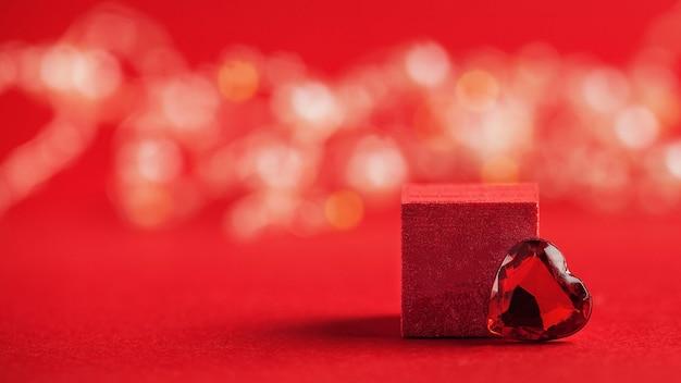 Podio vuoto per i tuoi prodotti con un cuore su uno sfondo rosso con il concetto di bokeh di san valentino