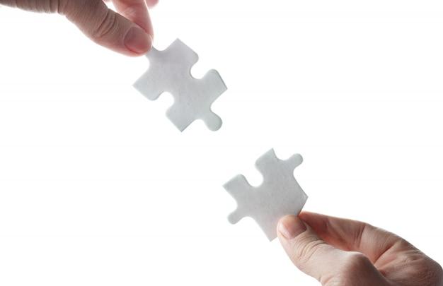 Puzzle vuoti nelle mani su una superficie bianca