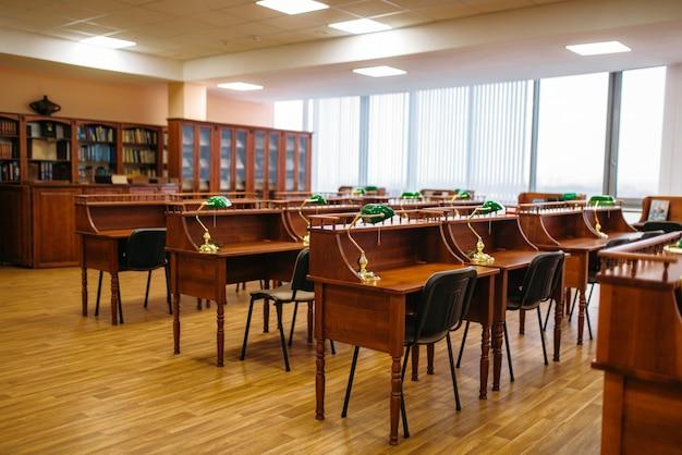 Sala di lettura vuota, file di tavoli in biblioteca, nessuno. deposito di conoscenza, scaffale con libri, concetto di educazione