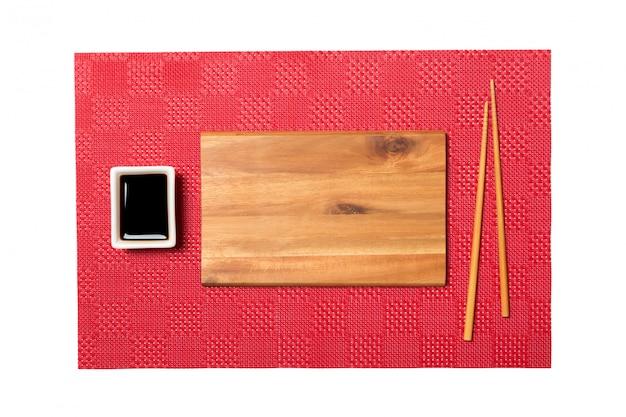 Svuoti il piatto di legno marrone rettangolare con le bacchette per i sushi e la salsa di soia sul fondo rosso dei sushi della stuoia. vista dall'alto con spazio di copia per il tuo design