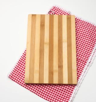 Tagliere da cucina in legno rettangolare vuoto e asciugamano rosso in una gabbia bianca su un tavolo bianco, vista dall'alto