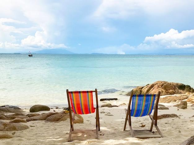 Lettini rossi e blu vuoti sulla spiaggia di sabbia con rocce sullo sfondo del cielo e del mare in una giornata di sole.
