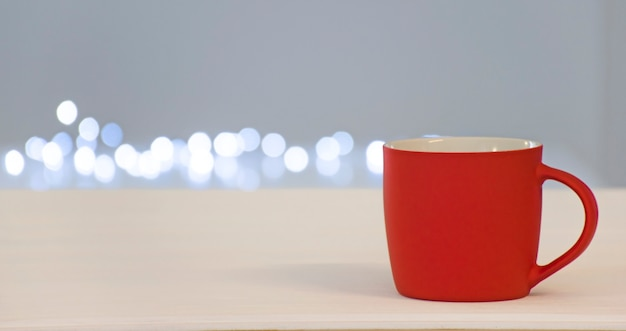 Tazza rossa vuota con spazio libero per testo o emblema con luci bokeh accese