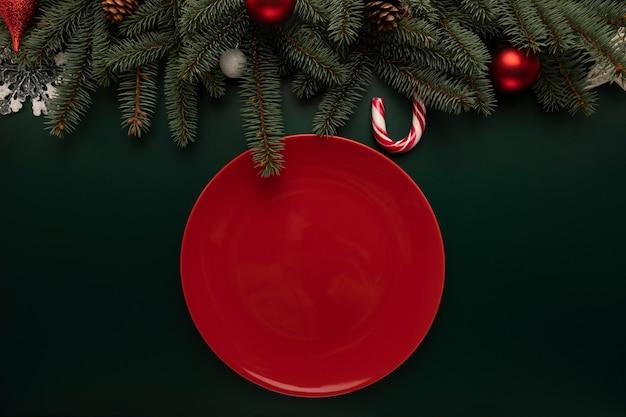 Un piatto rosso vuoto si trova sulla tavola di natale.