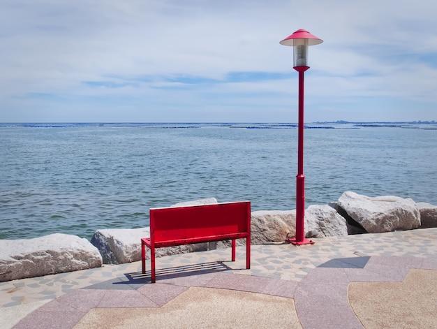 Panchina in legno rossa vuota e palo di illuminazione in riva al mare