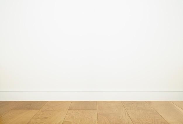 Interno vuoto della stanza con il fondo bianco della parete e pavimento di legno vuoto