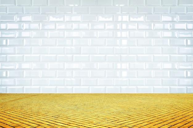 Stanza vuota con muro di piastrelle di ceramica bianca e pavimento a mosaico dorato