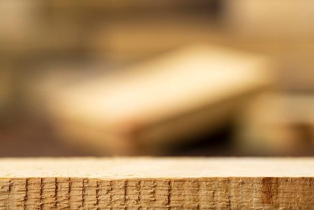 Tavolo in legno grezzo vuoto con scena sfocata per vetrina di prodotti con posto per testo o foto.