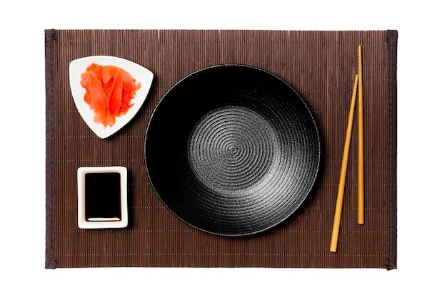 Piatto nero rotondo vuoto con le bacchette per sushi, zenzero e salsa di soia su sfondo scuro stuoia di bambù. vista dall'alto con copia spazio per il tuo design.