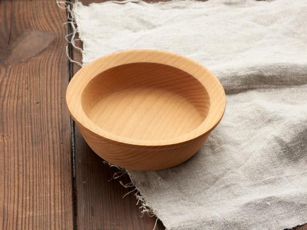 Svuoti il piatto marrone rotondo che sta su un tovagliolo di tela grigio