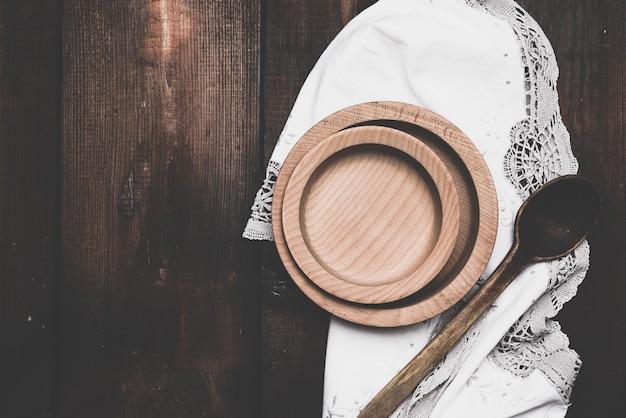 Piatto marrone rotondo vuoto in piedi su un tovagliolo bianco, fondo di legno da vecchie tavole