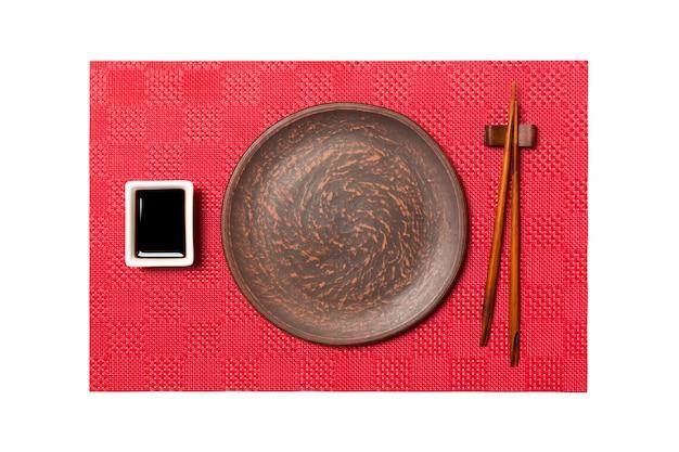 Piatto marrone rotondo vuoto con le bacchette per sushi e salsa di soia sul fondo rosso dei sushi della stuoia. vista dall'alto con copia spazio per il tuo design.