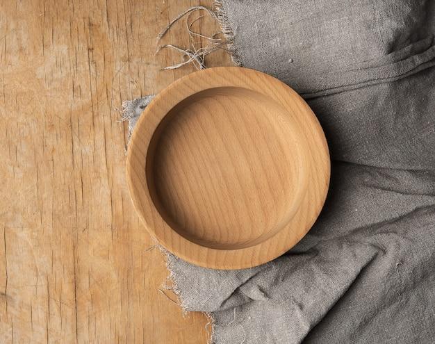 Piatto di legno marrone rotondo vuoto sul tavolo, vista dall'alto