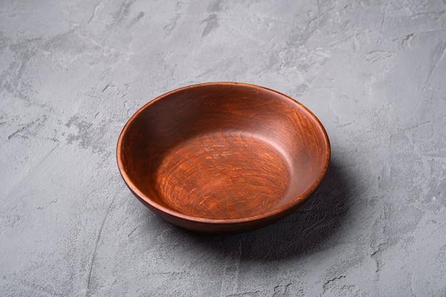 Piatto di legno marrone artigianale rotondo vuoto sulla superficie del calcestruzzo di pietra