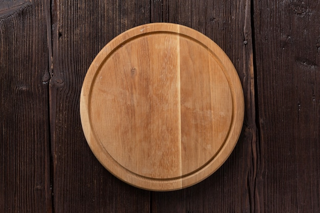 Pizza rotonda vuota o bordo del barbecue sulla tavola di legno scuro