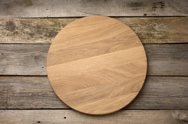 Tagliere da cucina in legno rotondo vuoto su superficie di legno, tavola per pizza, vista dall'alto