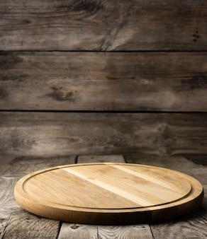 Tagliere da cucina in legno rotondo vuoto su superficie di legno, tagliere per pizza