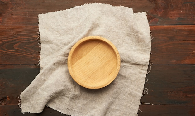 Piatto di legno rotondo vuoto sul panno