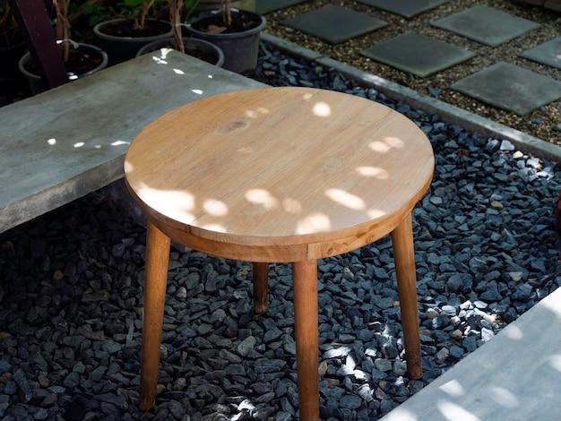 Tavolino rotondo in legno vuoto con semplice sedile in cemento sul pavimento di ghiaia vicino alla passerella nel giardino sul retro, vista dall'alto.