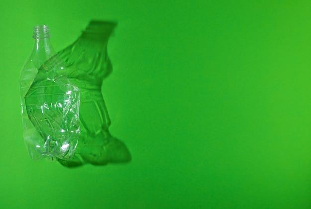 Bottiglia di plastica usata sgualcita vuota su sfondo verde
