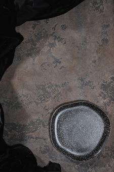 Piatto nero rustico vuoto su colore marrone