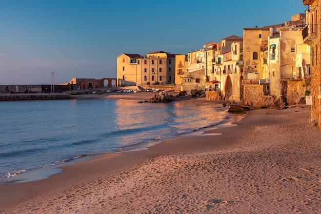 Spiaggia di sabbia vuota nel centro storico della città costiera cefalù al tramonto, sicilia, italy