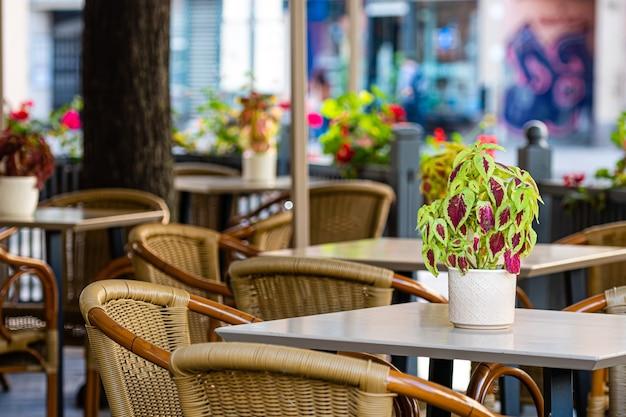 Tavoli e sedie serviti vuoti del caffè all'aperto