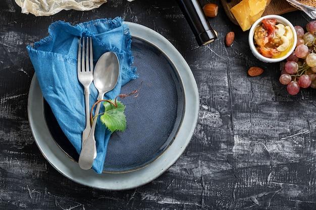 Piatto blu da portata vuoto con cucchiaio forchetta in cornice di ingredienti alimentari cucina mediterranea gastronomia antipasto snack uva formaggio vino. piatto piatto blu con copia spazio sul tavolo di cemento scuro.
