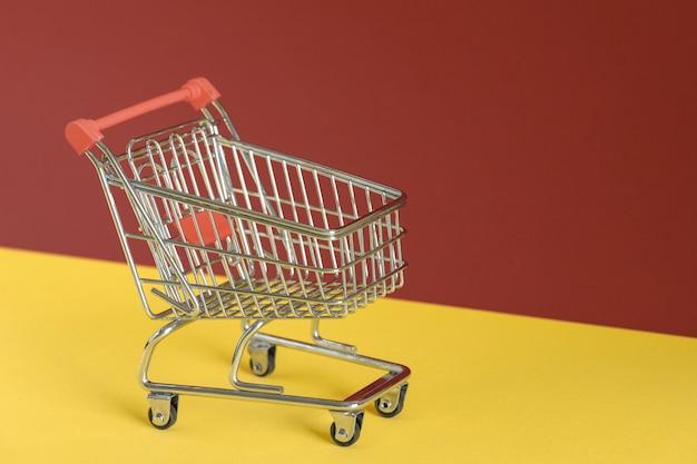 Carrello vuoto su sfondo colorato giallo e marrone. shopping online o concetto di e-commerce