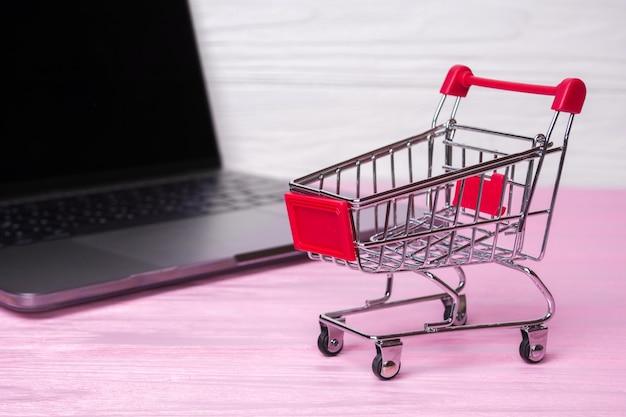 Carrello della spesa vuoto e un computer portatile su uno sfondo di legno rosa