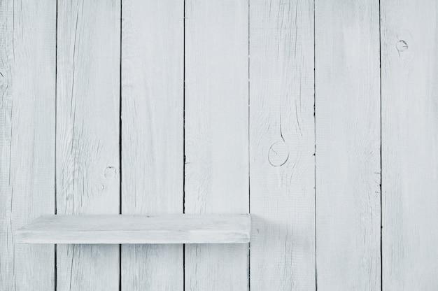 Scaffale corto vuoto da un albero. uno sfondo di legno.
