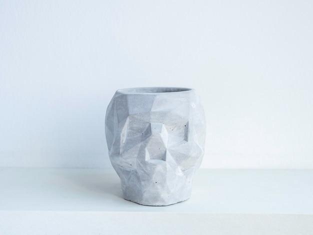 Vaso per piante in calcestruzzo a forma di teschio vuoto su mensola in legno bianco isolato su parete bianca piccola moderna fioriera in cemento fai da te decorazione alla moda.