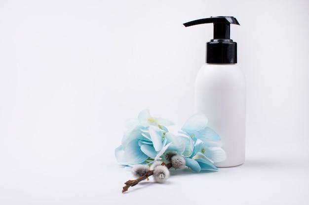 Bottiglia di sapone vuota e fiori blu isolati su sfondo bianco