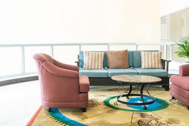 Divano vuoto e sedia con decorazione di cuscini in una stanza