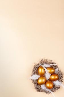 Spazio vuoto per il testo, un banner di buona pasqua. uova d'oro dipinte, piume bianche.