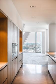 Cucina spaziosa vuota con armadi minimalisti contemporanei in appartamento attico di lusso con pavimento piastrellato