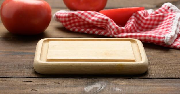 Tagliere di legno quadrato vuoto sul tavolo, accanto all'asciugamano da cucina rosso