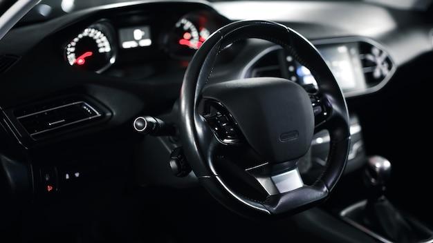 Volante vuoto in macchina piantone dello sterzo dell'auto interno di un'auto moderna premium con interni scuri del primo piano del volante