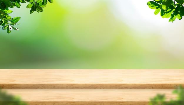 Piano d'appoggio di legno vuoto della plancia di punto con l'albero della sfuocatura in parco con il fondo della luce del bokeh