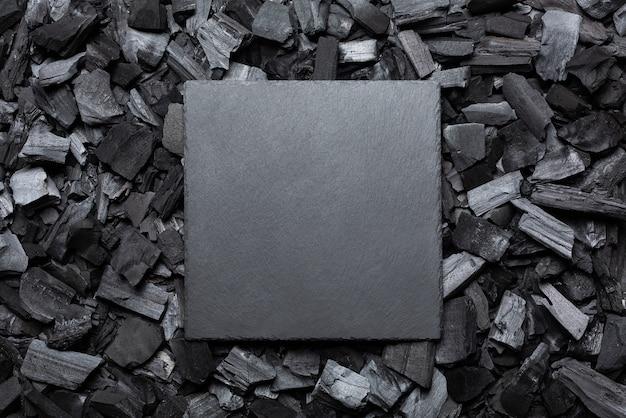 Piatto di pietra vuoto su carbone. la cornice quadrata è nera. copia spazio. posto per il testo.